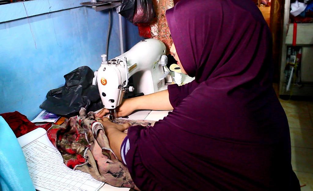 Dilla mengerjakan pesanan pakaian muslim. | Foto: Iman Jaya Lase