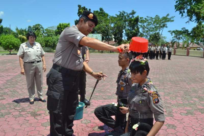Kapolres Nias AKBP Bazawatö Zevua menyiramkan air kembang di kepala perwakilan brigadir remaja yang baru tiba dan akan bertugas di Polres Nias, Kamis (24/3/2016). —Foto: Dokumentasi Humas Polres Nias